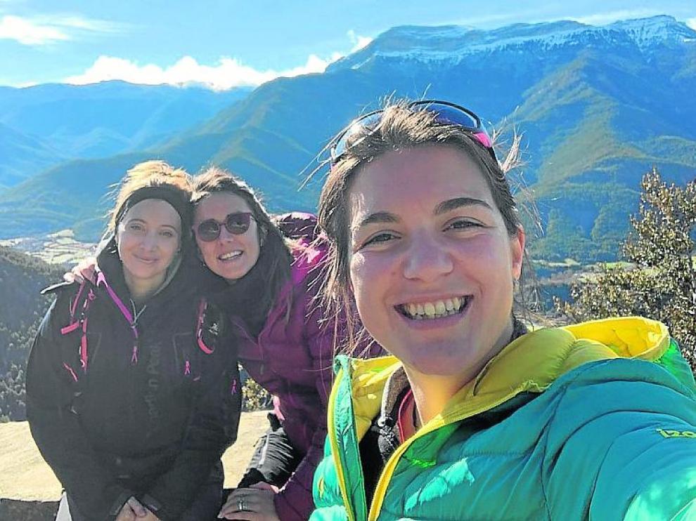 Alba Pueyo, Elena Jal y Ainhoa Viñuales posan con Fiscal y la Peña Canciás al fondo
