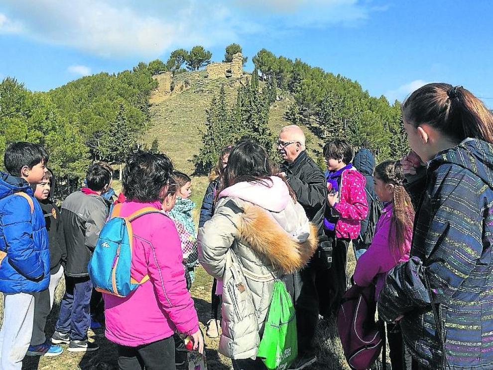 Chesús Jiménez explica a un grupo de escolares las ruinas del antiguo castillo de Ayerbe