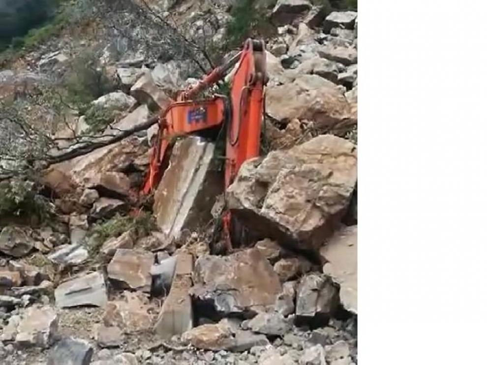 Imagen de la excavadora prácticamente sepultada bajo la avalancha de piedras.
