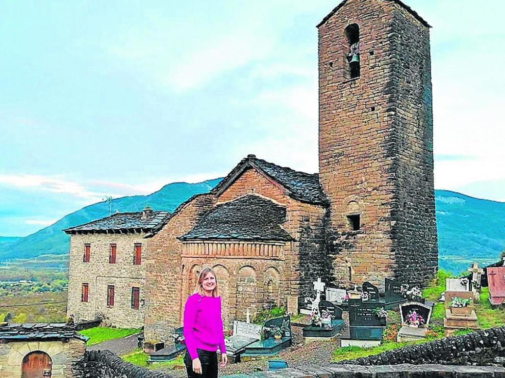 Mónica Ara, directora de la oficina de Caja Rural de Aragón en Jaca junto a la iglesia de su pueblo: Oliván