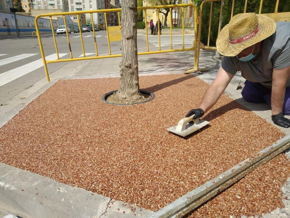 Un operario coloca materiales permeables en los alcornoques.