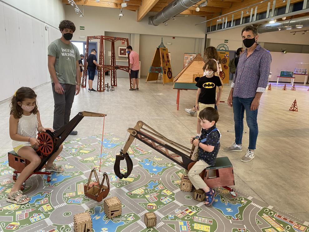 Los niños pueden desplazar cubos de madera con dos grúas de juguete.