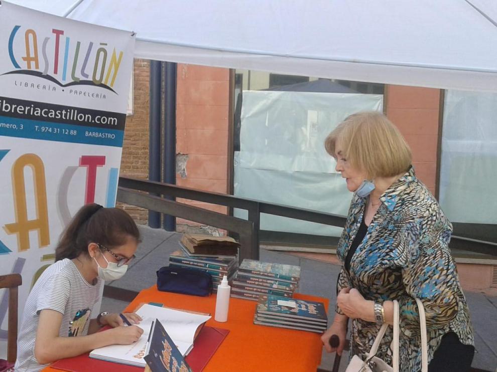 La autora Irene Mora Borruel, firmando varios ejemplares a los barbastrenses.