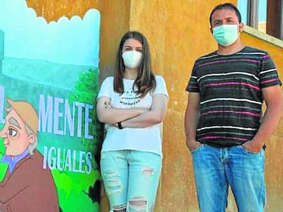 La artista María Salinas junto al alcalde de Lascuarre, José Luis Lloret, junto al mural pintado en el casco urbano.
