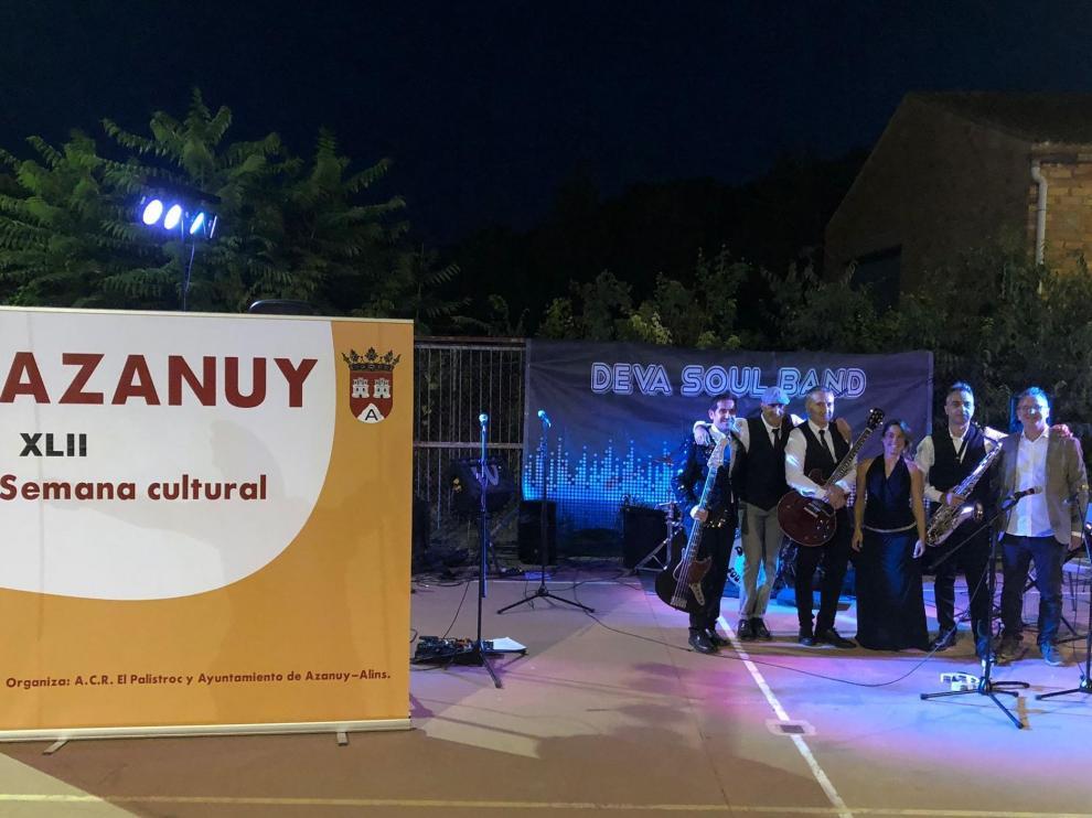 En la imagen, los miembros de Deva Soul Band junto al cartel de las jornadas culturales.