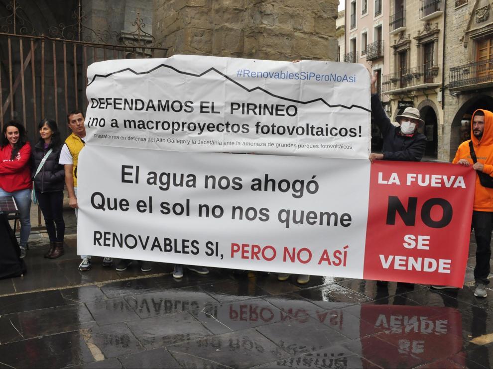 Representantes de las diferentes plataformas comarcales mostraron pancartas contra los macroparques solares a las puertas de la Catedral de Jaca.