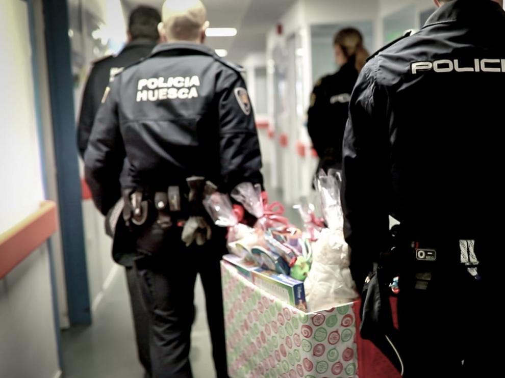 Agentes de Policía Local y Nacional de Huesca llevan los primeros regalos de Reyes a los niños del Hospital San Jorge