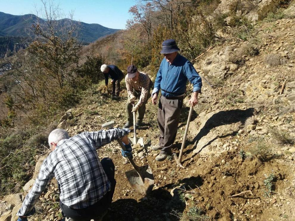 Vecinos de Yebra limpian un derrumbe de tierra en el camino de Santa Orosia