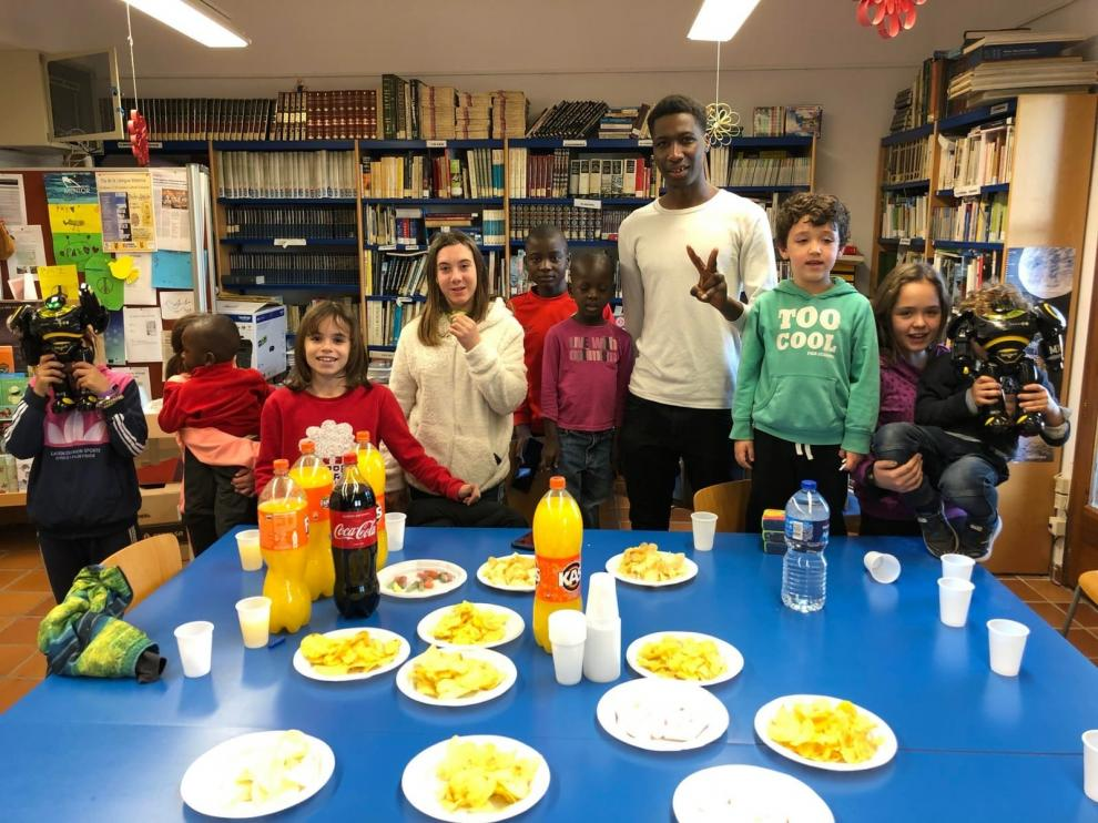 Niños de Fonz enseñan castellano a vecinos inmigrantes en la Biblioteca Municipal