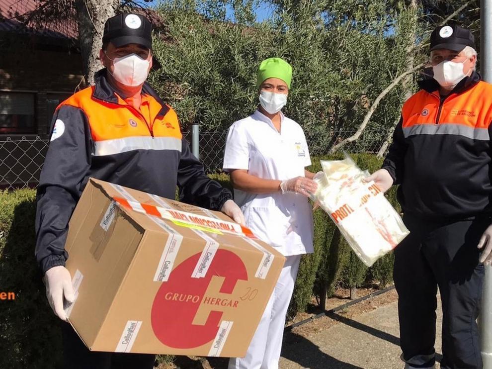 Protección Civil del Somontano reparte batas biodegradables para la protección ante el coronavirus por varios centros
