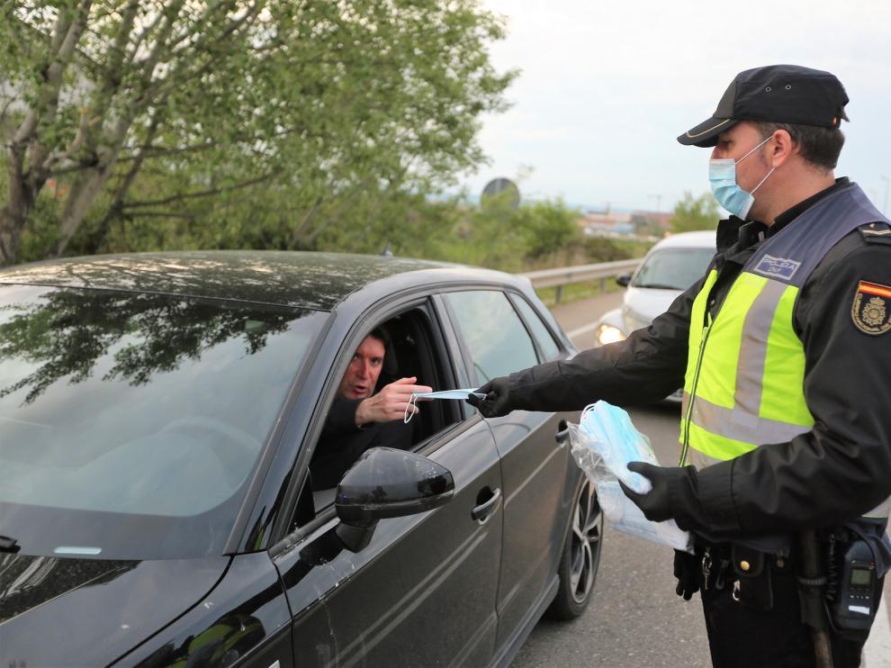 Policía y Protección Civil reparten mascarillas a los oscenses que iban a trabajar