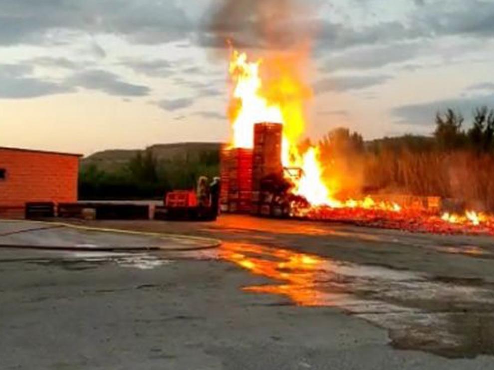 """El fuego quema los """"palots"""" apilados en el exterior de un almacén de fruta en Fraga"""
