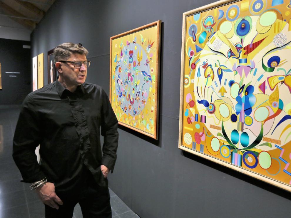 José Ángel Enciso junto a dos de los cuadros que expone en el Centro Manuel Benito.