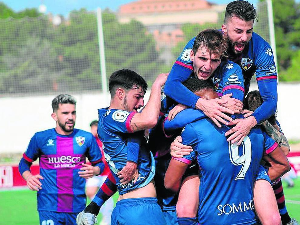 Los jugadores del Huesca B se abrazan con Carlos Kevin tras marcar el gol de la victoria.