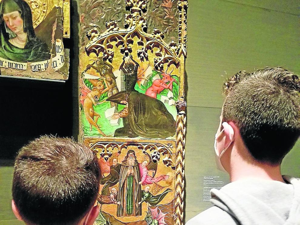 Dos niños miran el Retablo de San Antonio Abad de Monzón, expuesto en el Museo de Lérida.