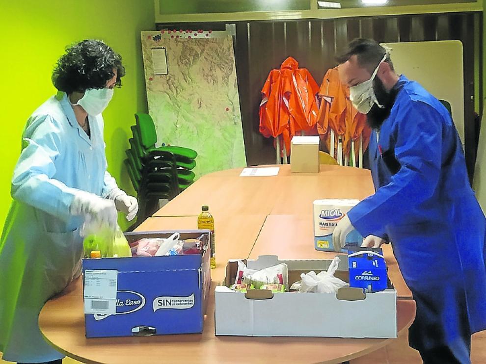Trabajadores del centro logístico preparando los lotes de alimentos para llevar a vecinos confinados.