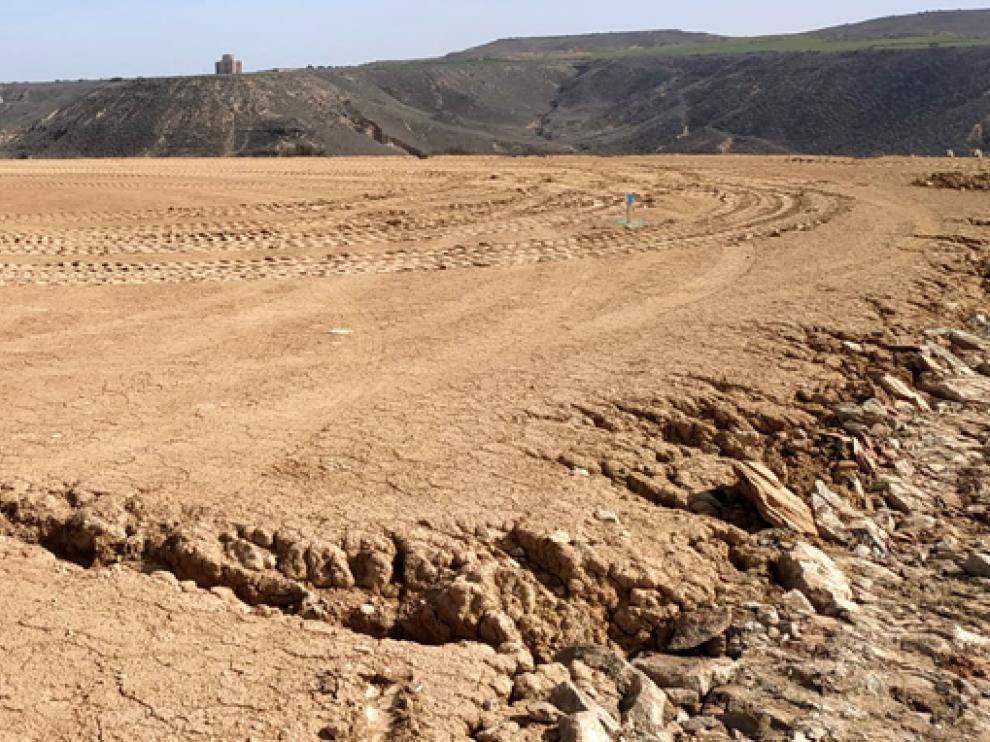 Imagen de un terreno con la ermita de Chalamera al fondo.