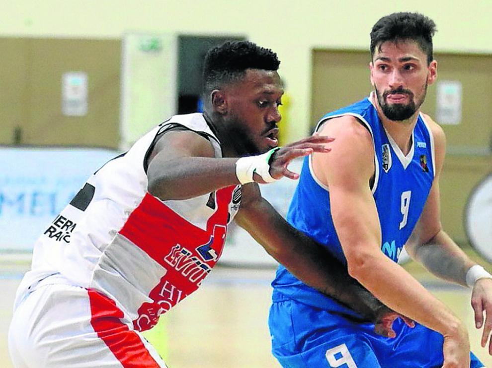 Mike Moore, defendiendo en Melilla, es el indicado para frenar el juego en el poste bajo de Cáceres de Barber y Schaftenaar.