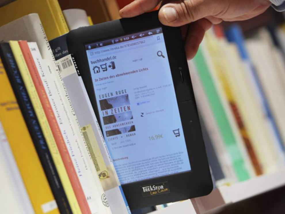 Una persona observa un libro electrónico en un estante de la Feria del Libro de Fráncfort (Alemania).