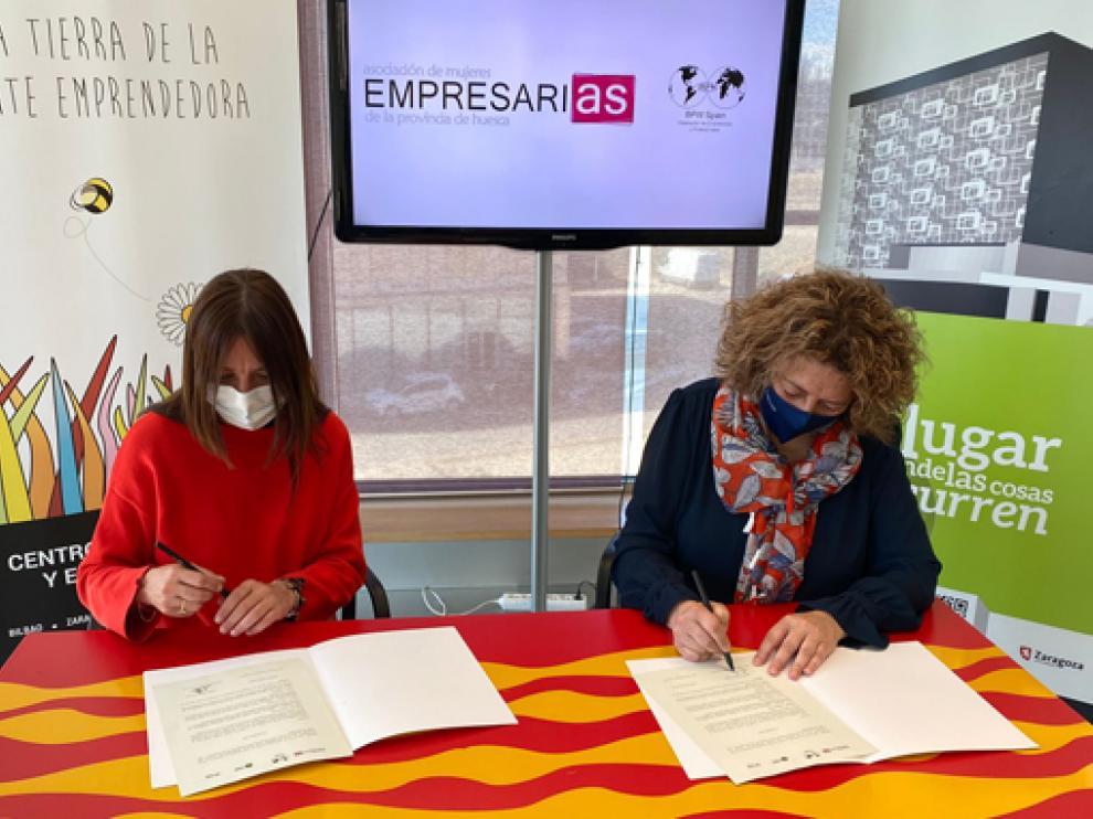Carmen Fernández y Romy Piñeyroa firman el convenio entre ambas entidades.