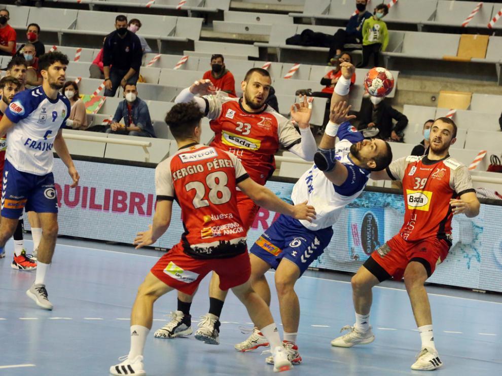 El pivote Esteban Salinas trata de cazar un balón ante los defensores oscenses.