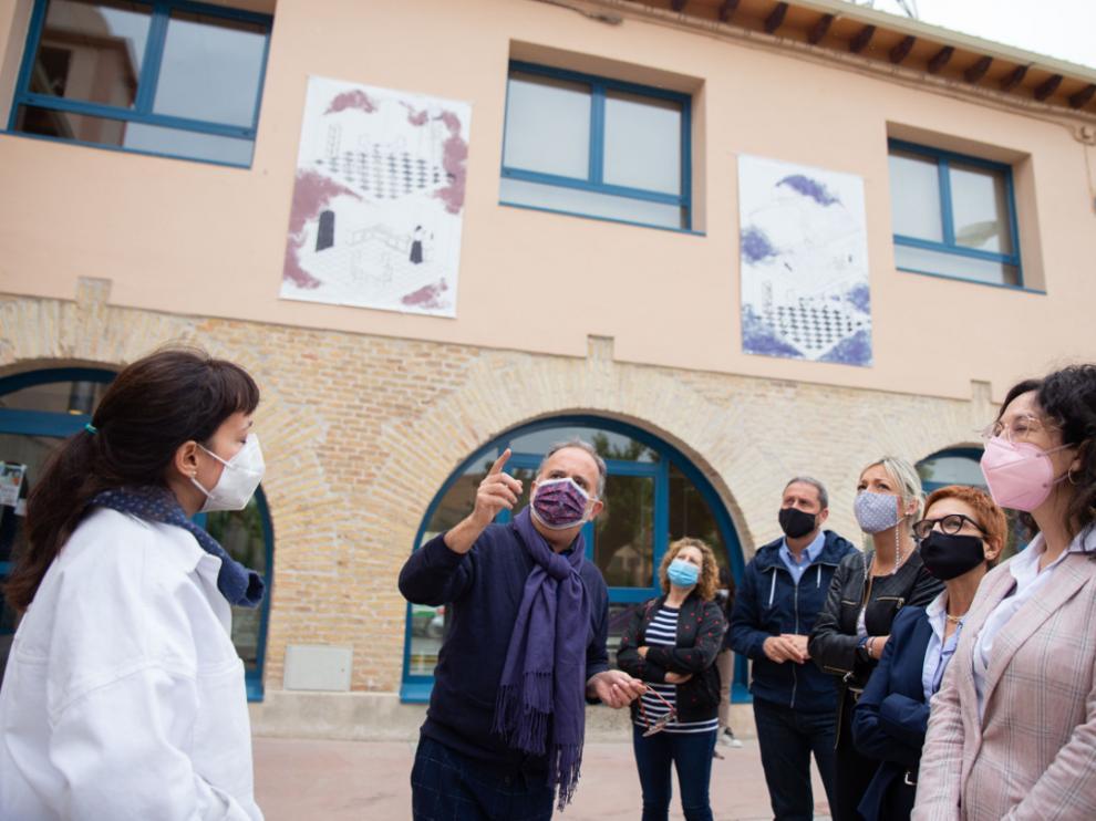 Fotografía de grupo mostrando las ilustraciones instaladas en el exterior de la biblioteca de Sariñena