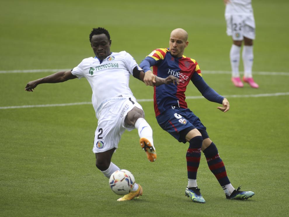 Sandro pelea con Djené por hacerse con el balón en el Huesca-Getafe.