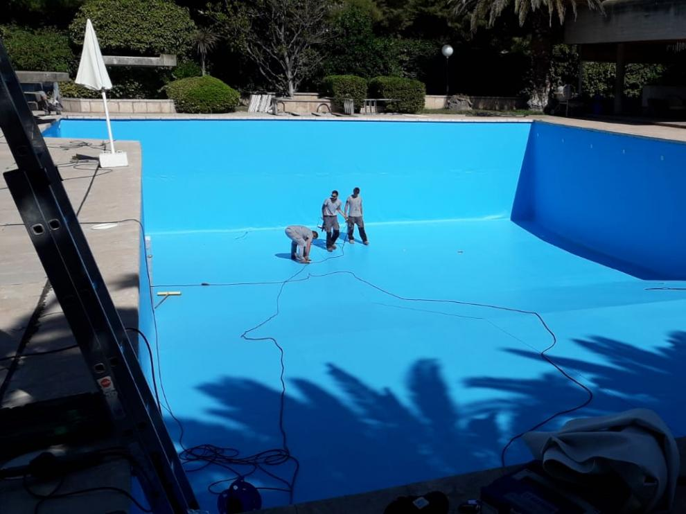 Empleados de Arizón y Gracia trabajando en la rehabilitación y mantenimiento de una piscina.