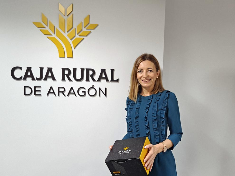 La directora de Particulares y Marketing de Caja Rural de Aragón, Susana Álvarez, con la caja de la gorra verde.
