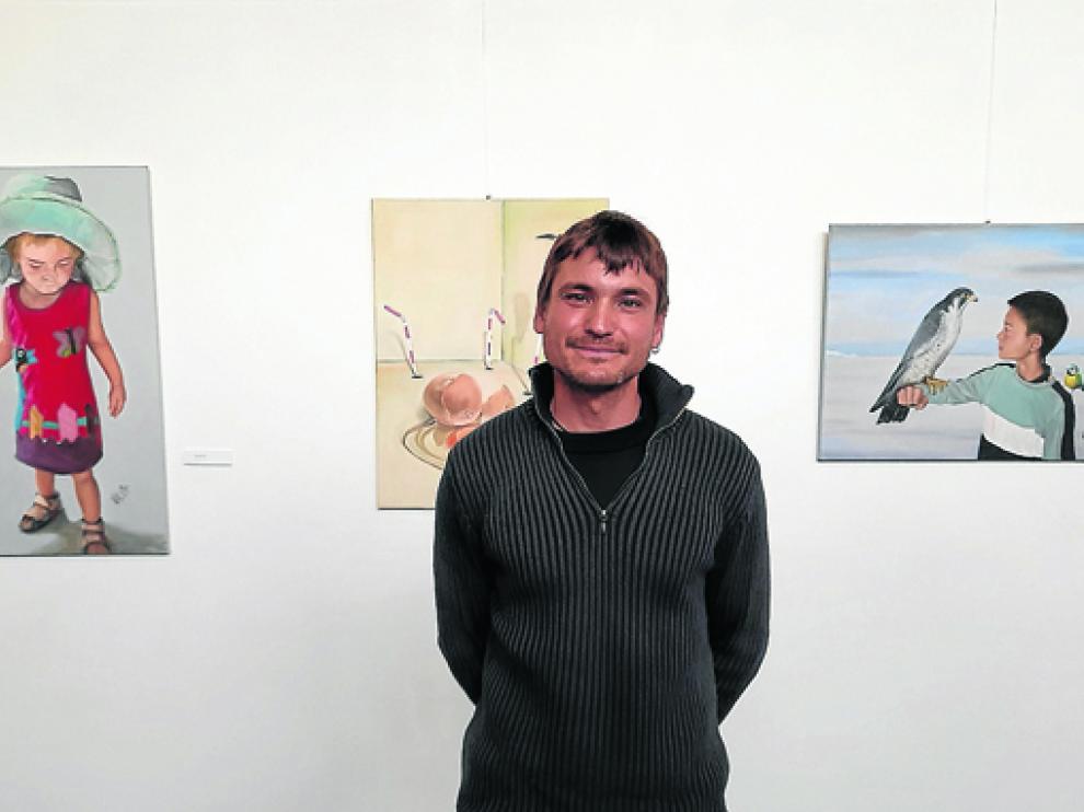 Javier Valero junto a tres de las obras que conforman la exposición Efluvios gráficos.