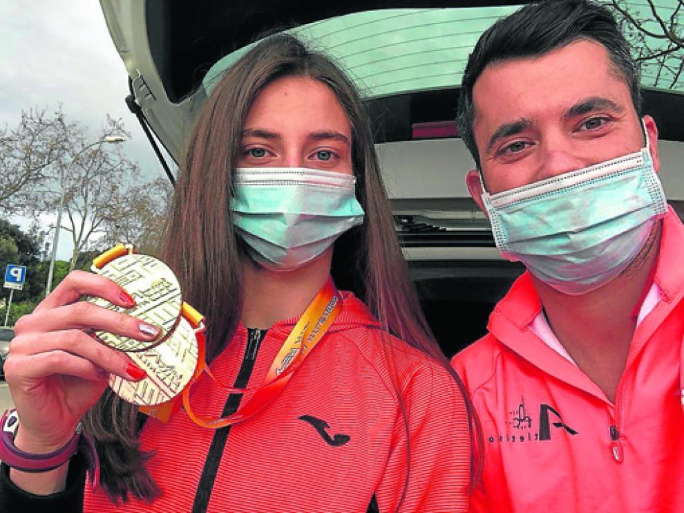 Elena Guiu con su entrenador Eloy Mur y las dos medallas del último nacional.