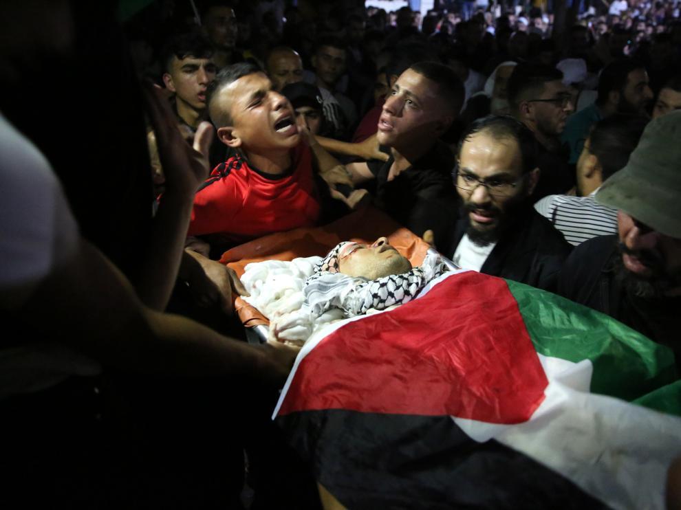 Los palestinos trasladan un cadáver, en medio del dolor.