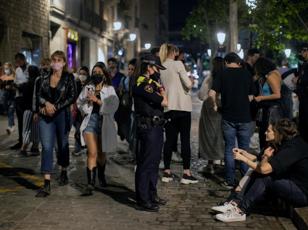 Una agente de policía pide a una pareja que se ponga la mascarilla, en la zona del Born de Barcelona, durante la noche del sábado.