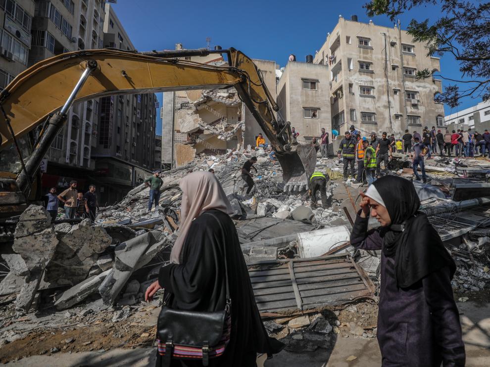 Civiles palestinos realizan labores de búsqueda de personas bajo los escombros de un edificio en Gaza.