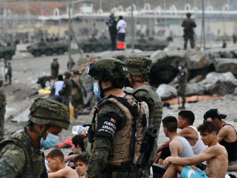 Militares españoles vigilan las devoluciones en caliente que se están haciendo a los inmigrantes que han entrado a Ceuta por Marruecos.