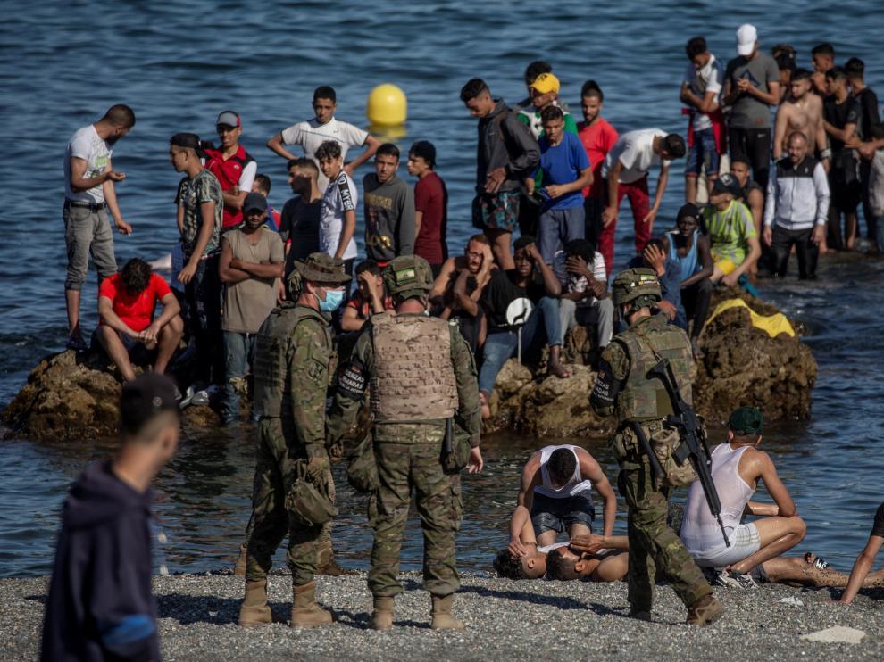 Soldados del Ejército de Tierra observando a un grupo de inmigrantes que llegaban a la costa de Ceuta.