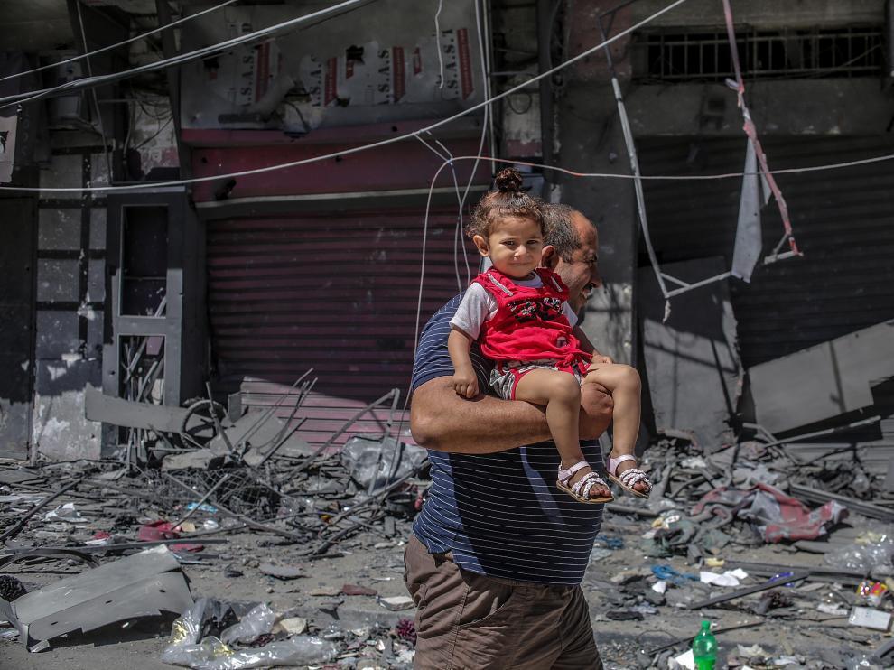Un hombre palestino huye con su hija en brazos después del ataque ayer a una torre en la ciudad de Gaza.