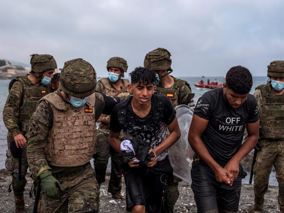 Soldados del Ejército ayudan a dos jóvenes a salir del agua en la playa de El Tarajal de Ceuta.
