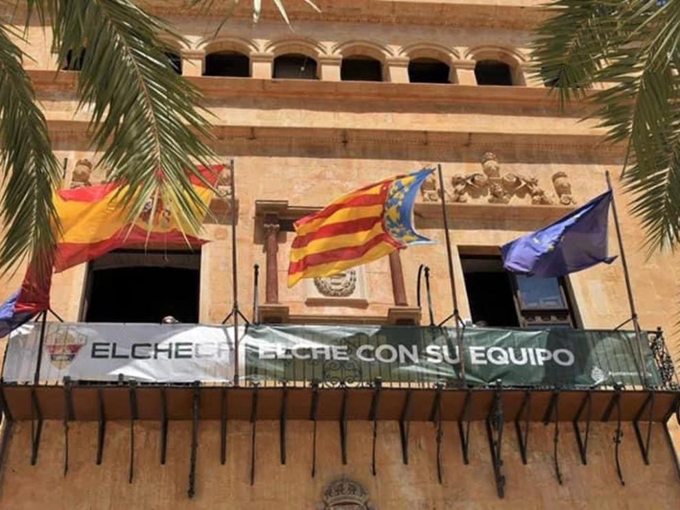 El Ayuntamiento de Elche ha colgado una pancarta de apoyo al equipo en su balcón.