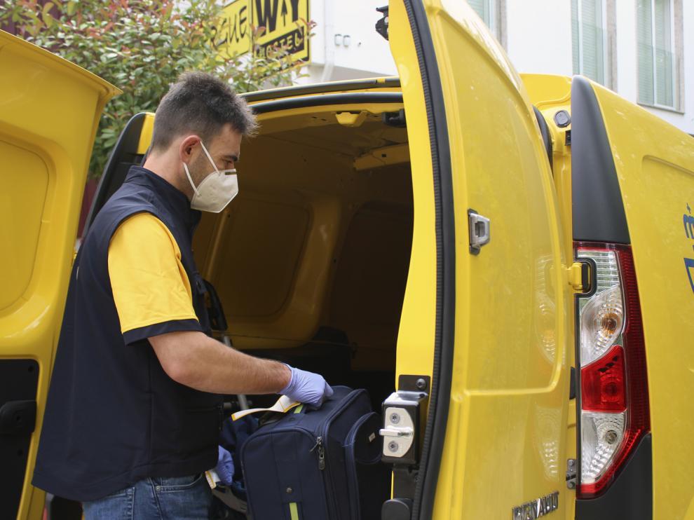Un trabajador de la empresa de Correos introduce una maleta en una furgoneta de reparto.