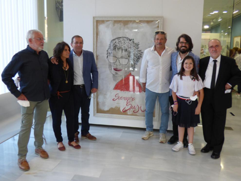 Marina Abarca (izda.), con el resto de la familia de Susi Lachén junto al retrato que preside la exposición.