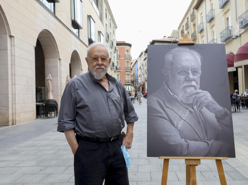 Gonzalo Suárez, posando con su retrato en los Porches de Galicia.