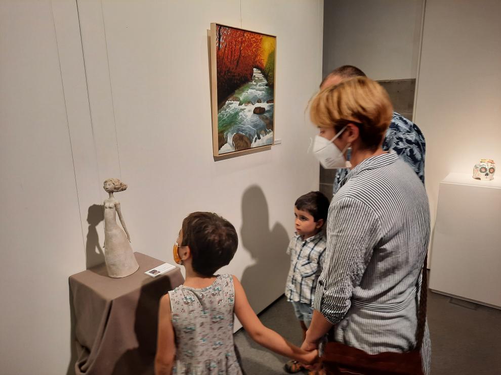 Una familia visitando la exposición en el Espacio Pirineos.