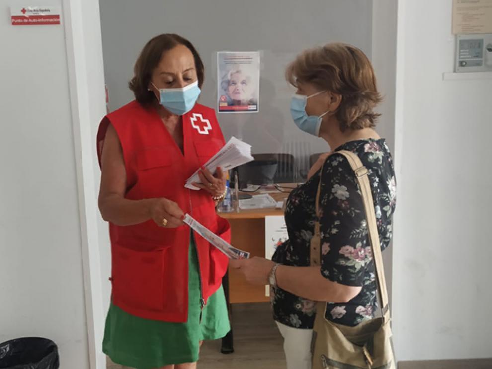 Una voluntaria reparte folletos informativos de la campaña de Cruz Roja contra el maltrato a mayores.