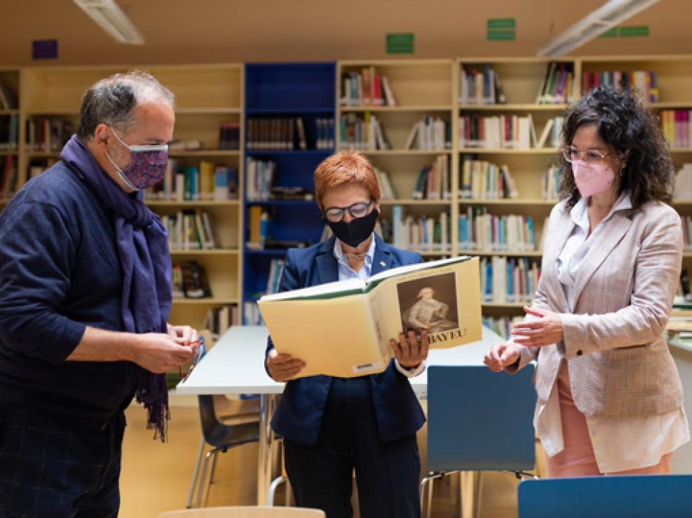 La diputada de Cultura Maribel de Pablo examina un libro sobre Bayeu en la biblioteca pública municipal de Sariñena.