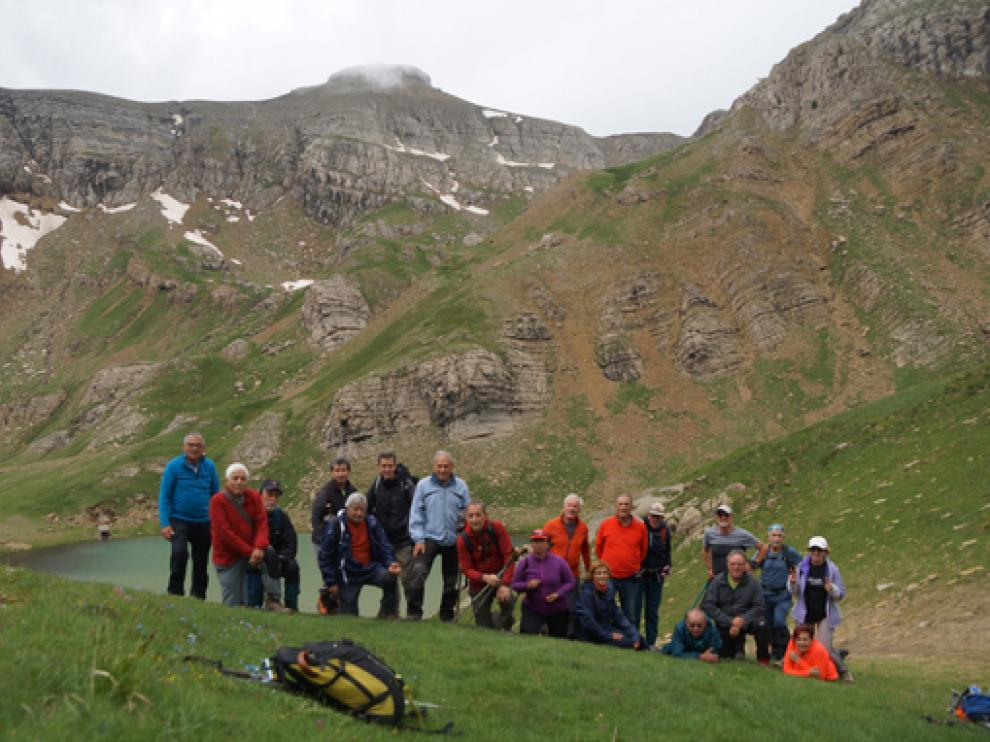 El grupo, frente al ibón y el paisaje montañoso al fondo.