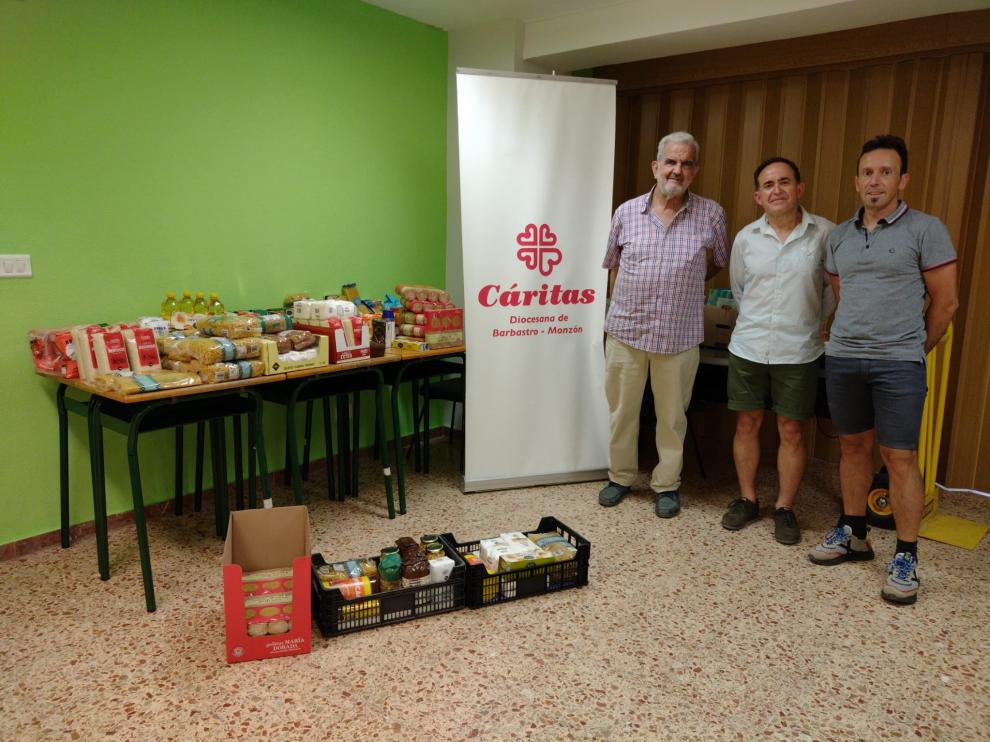 Fernando Latorre y Alejandro Castarlenas junto los alimentos donados a Cáritas.