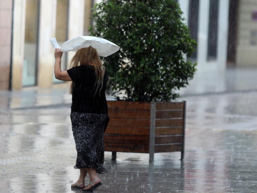 Una señora se resguarda de la lluvia con una bolsa de plástico.