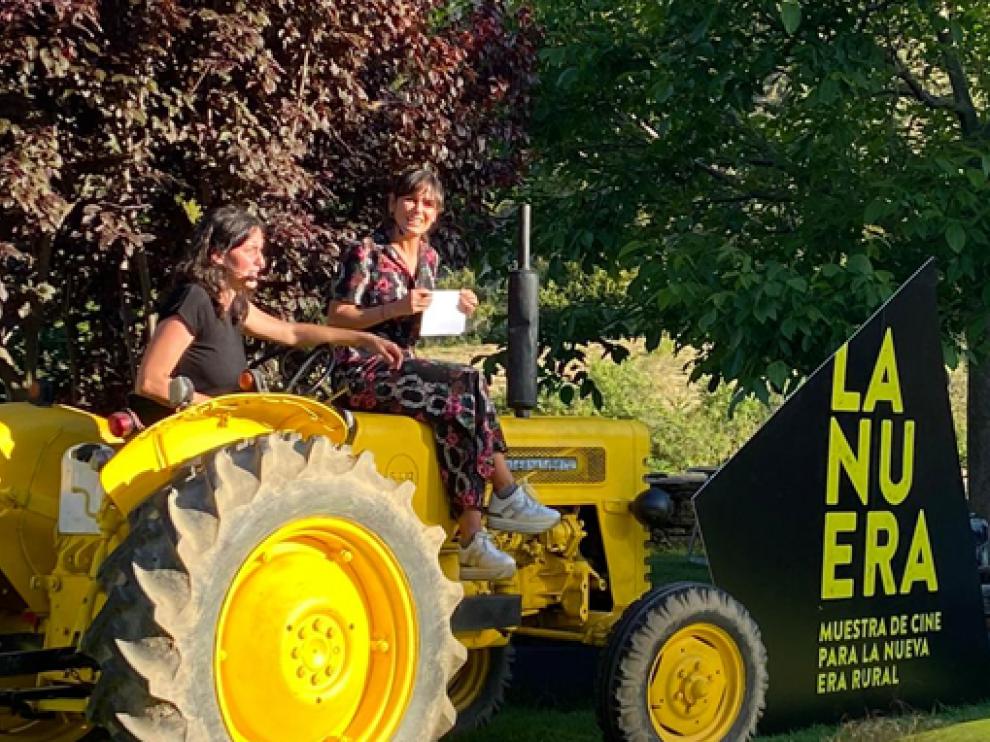 Elena S. Sánchez (derecha), subida al tractor que aparecía en el cartel, durante su inauguración.
