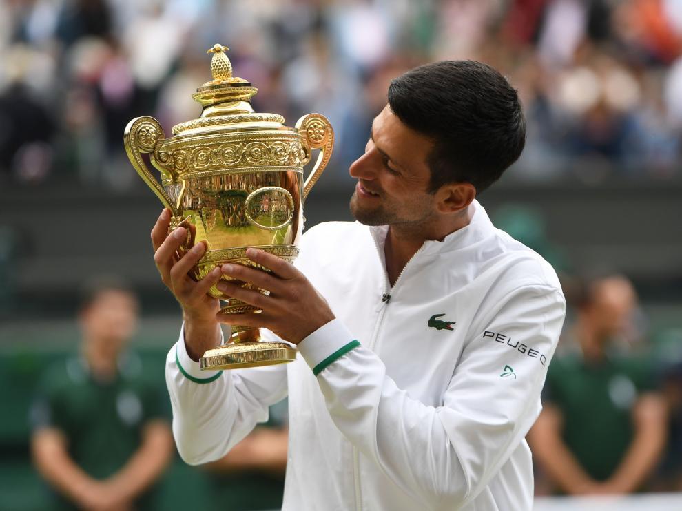 Djokovic mira al trofeo de campeón en la pista central de Wimbledon.